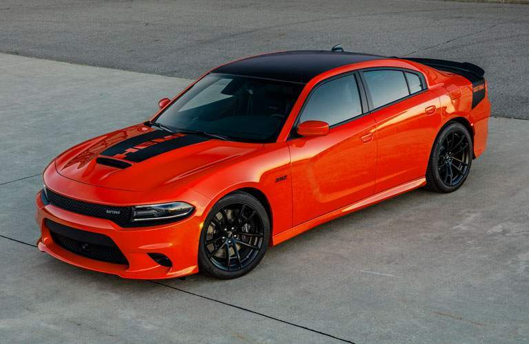 front and side view of orange and black 2018 dodge charger