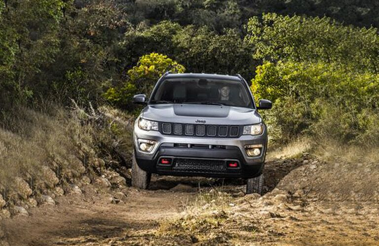 front view of silver 2018 jeep compass driving on dirt trail