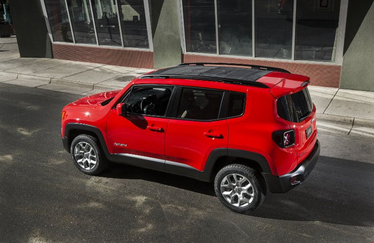 red jeep renegade on road by building