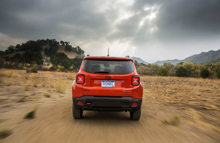 rear of red jeep renegade on dirt