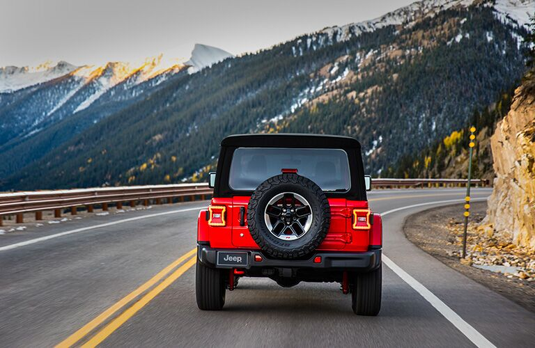 rear view of red 2018 jeep wrangler driving on highway with mountain ahead of it