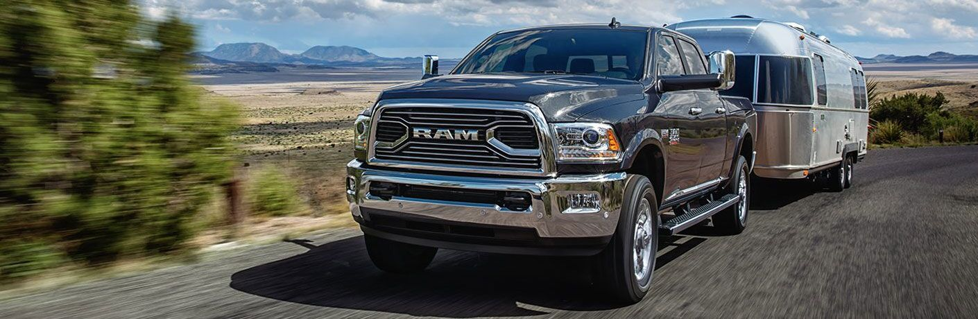 Black 2018 ram 2500 towing chrome trailer across desert road