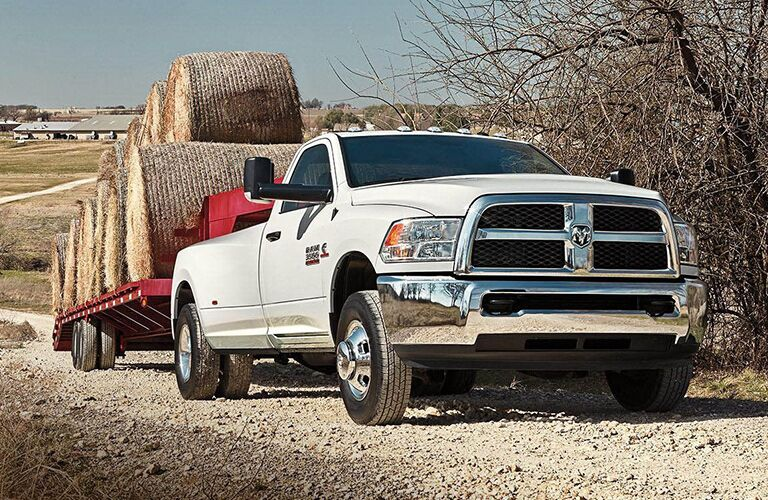 front and side view of white 2018 ram 3500 towing large trailer with hay bails
