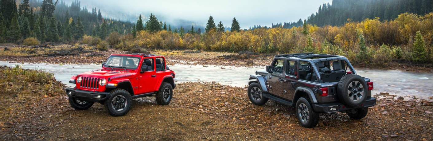 red and black jeep wranglers parked on dirt by river
