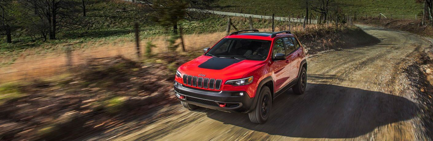 red and black 2019 jeep cherokee driving on dirt farm road