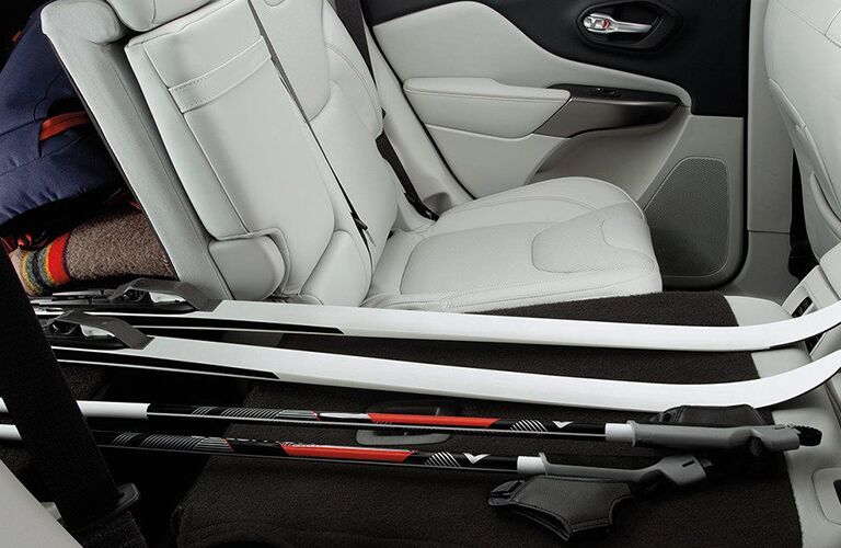 rear interior of 2019 jeep cherokee with rear seats folded and skis on seats