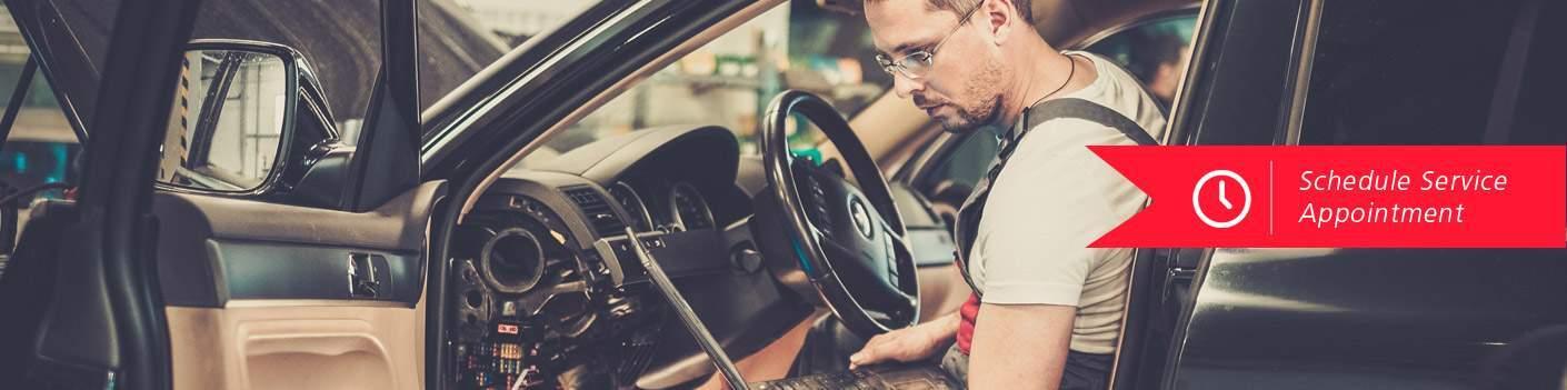 mechanic sitting inside car with hood up