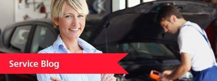 woman smiling as man inspects car