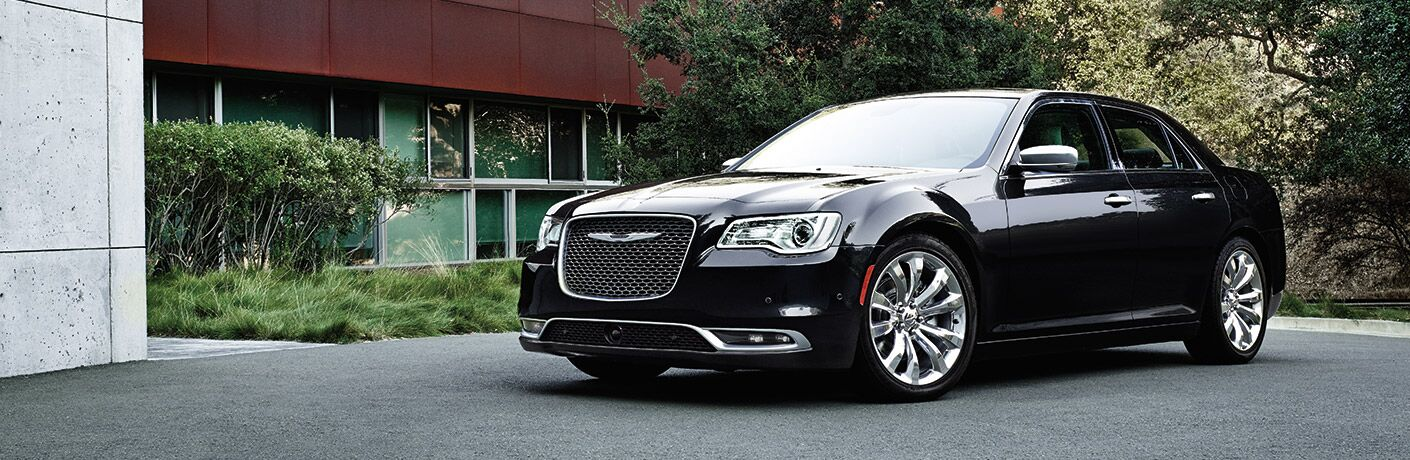 Exterior view of a black 2015 Chrysler 300 parked outside a home