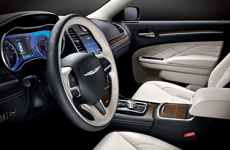 Interior view of the steering wheel and tan front seats of a 2015 Chrysler 300