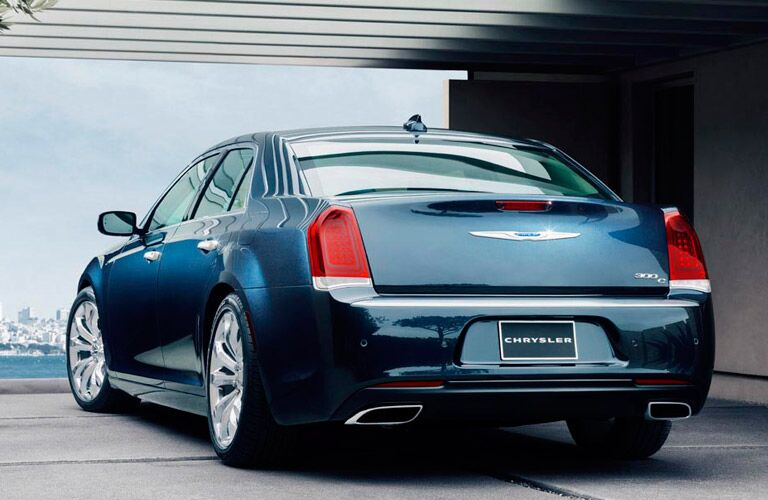 Exterior view of the rear of a blue 2015 Chrysler 300 exiting a garage