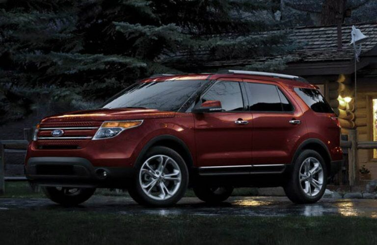 Exterior view of a red 2015 Ford Explorer parked outside a cabin in the woods
