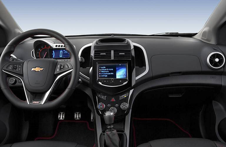 Interior view of 2016 Chevy Sonic showing steering wheel and infotainment system touch screen
