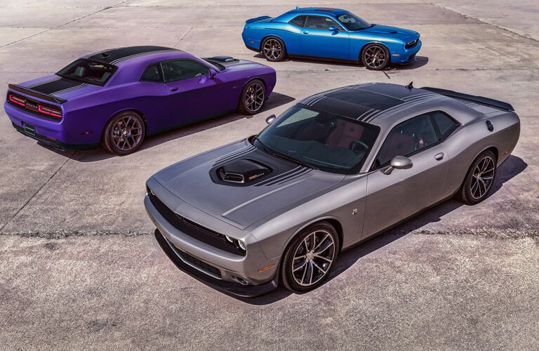 Exterior image of a three 2016 Dodge Challenger models that are purple, silver and blue