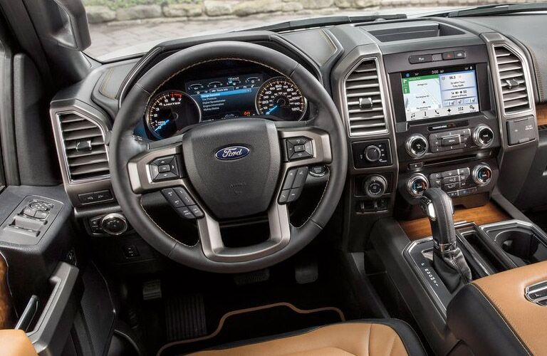 Interior view of a black steering wheel and touchscreen of a 2016 Ford F-150