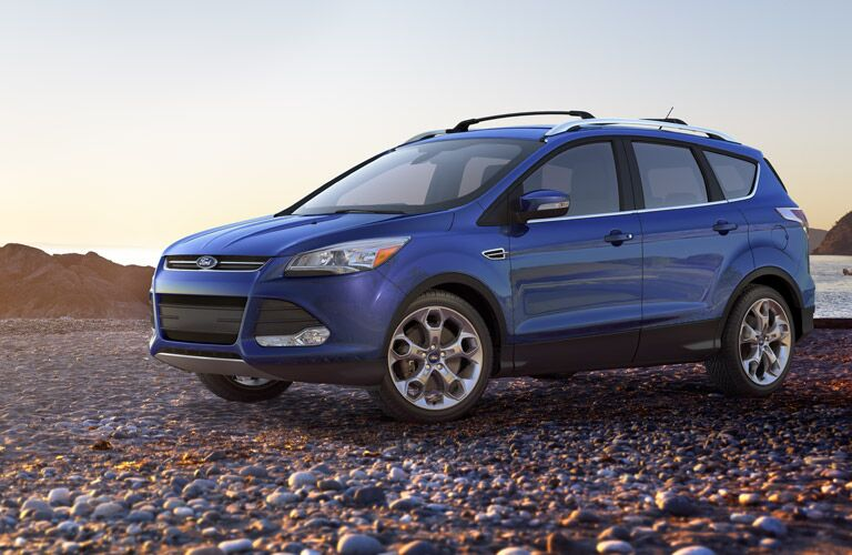 Exterior view of a blue 2016 Ford Escape parked on a rock-covered shoreline
