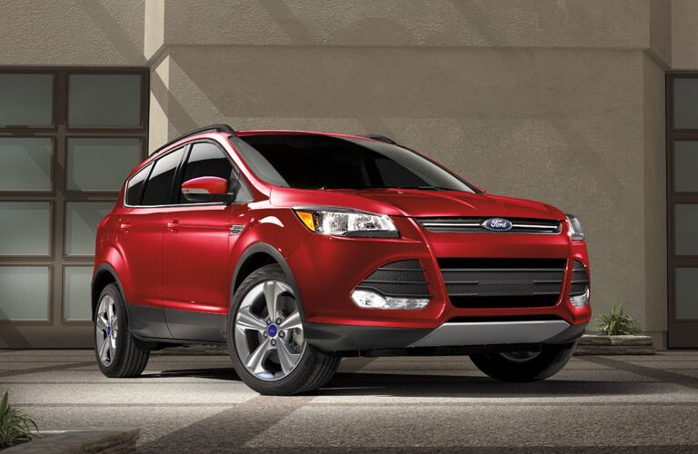 Exterior view of a red 2016 Ford Escape parked in a driveway outside a home