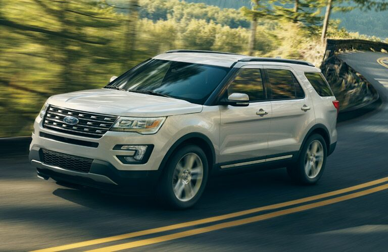 Exterior view of a silver 2016 Ford Explorer driving down a two-lane country highway