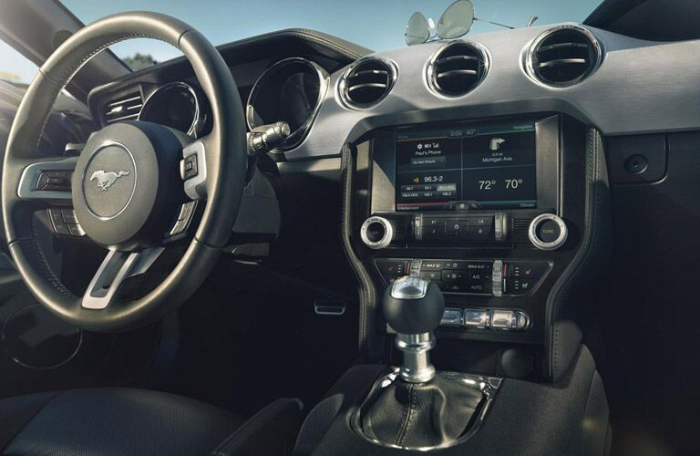 Interior view of the black steering wheel and touchscreen inside a 2016 Ford Mustang