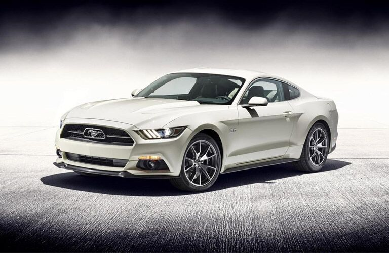 Exterior view of a white 2016 Ford Mustang parked in an empty showroom