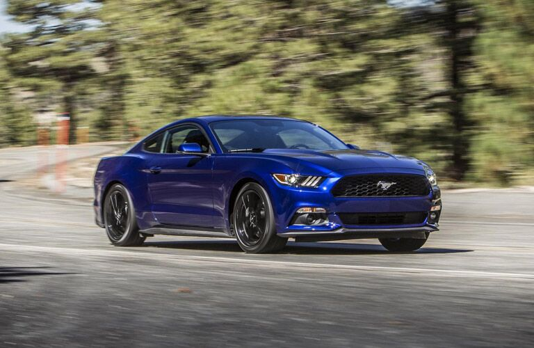 Exterior view of a blue 2016 Ford Mustang driving around a bend in the road