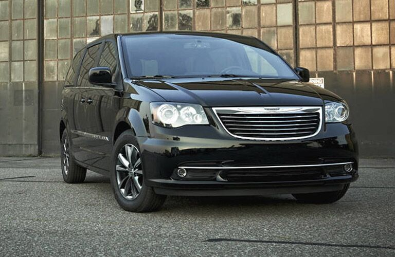 Exterior view of a black 2016 Chrylser Town & Country parked outside a warehouse