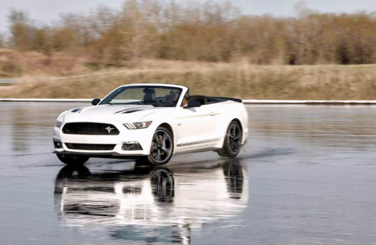 white 2016 Ford Mustang Convertible on wet cement exterior front driver side view