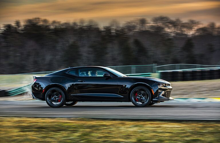 Exterior view of a black 2017 Chevrolet Camaro driving around an empty race track