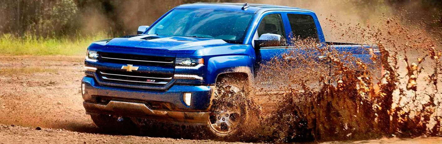 Exterior view of a blue 2017 Chevrolet Silverado 1500 driving through mud