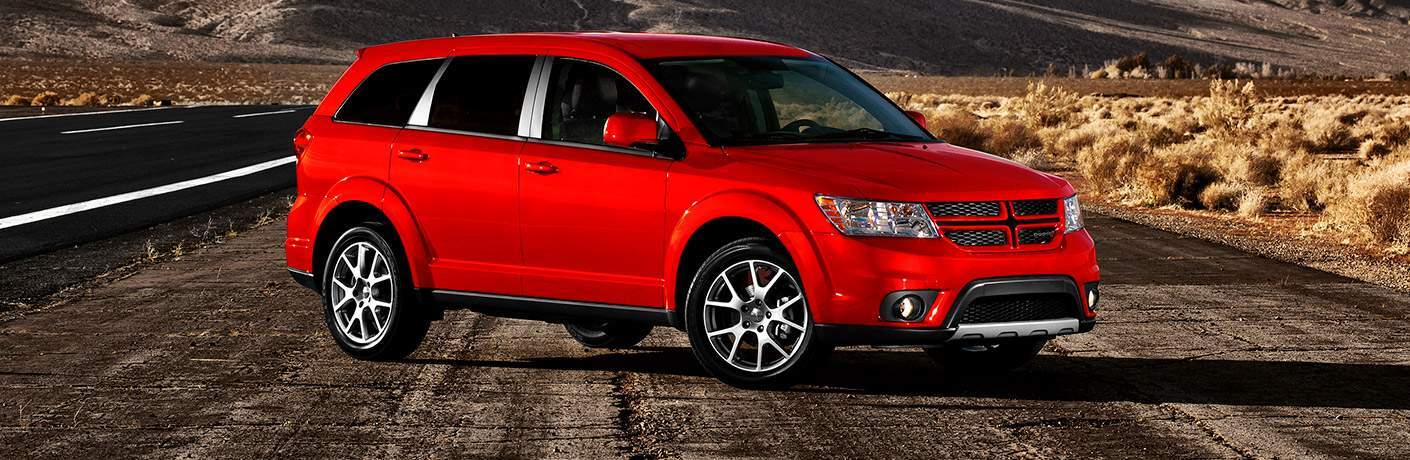 Exterior view of a red 2017 Dodge Journey parked along a desert highway