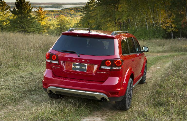 Exterior view of the rear of a red 2017 Dodge Journey driving down a dirt trail