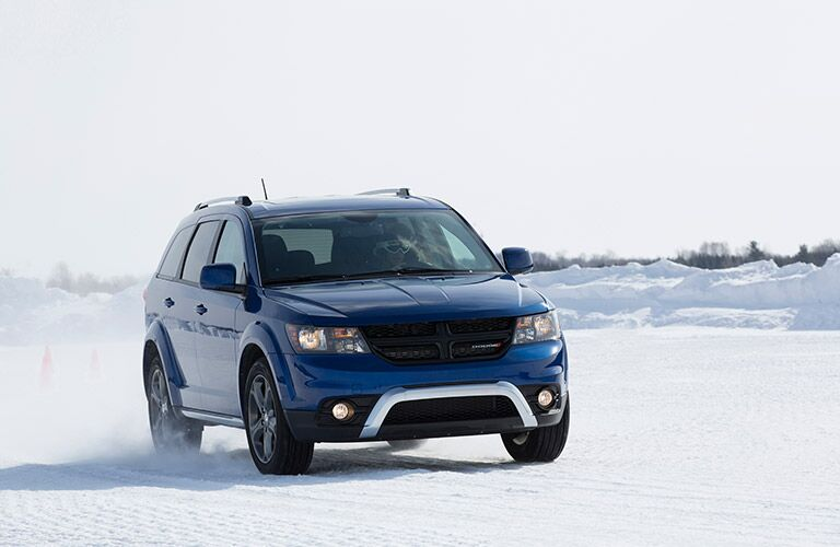 Exterior view of the front of a blue 2017 Dodge Journey parked in the snow