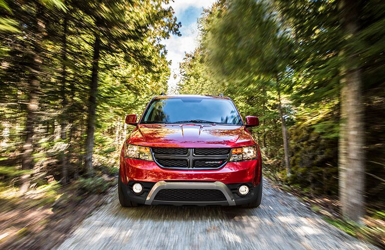 Exterior view of the front of a red 2017 Dodge Journey driving down a trail in the woods