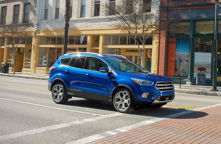 blue 2017 Ford Escape driving on city street