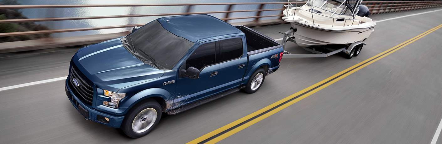 blue 2017 Ford F-150 towing a boat