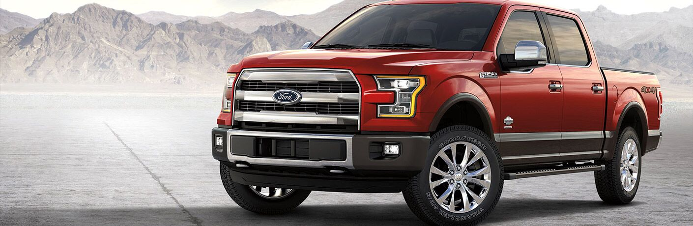 Exterior view of a red 2017 Ford F-150 parked on pavement with mountains in the background