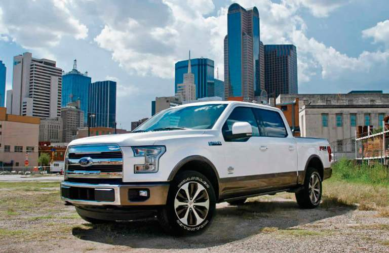 white 2017 Ford F-150 with city skyline behind it