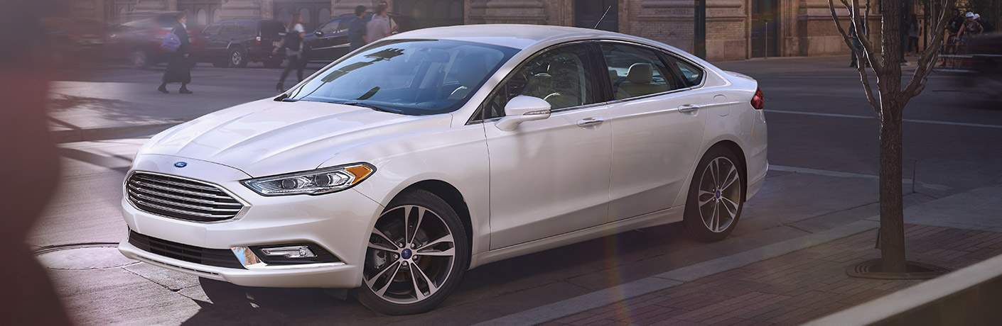 Exterior view of a white 2017 Ford Fusion parked on a city side street