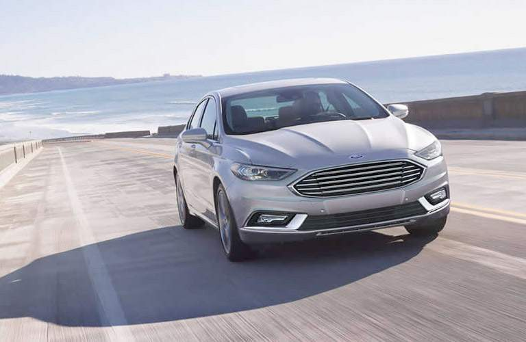 Exterior view of a silver 2017 Ford Fusion driving down a two-lane highway
