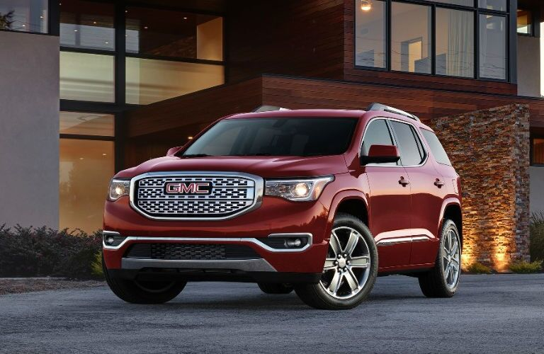 Exterior view of a red 2017 GMC Acadia parked in a home's driveway