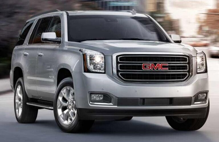 Exterior view of a silver 2017 GMC Yukon parked in the middle of a city street