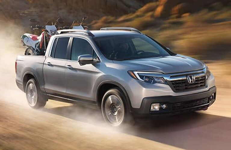 Exterior view of a silver 2017 Honda Ridgeline driving down a dirt road with dirt bikes in the truck bed