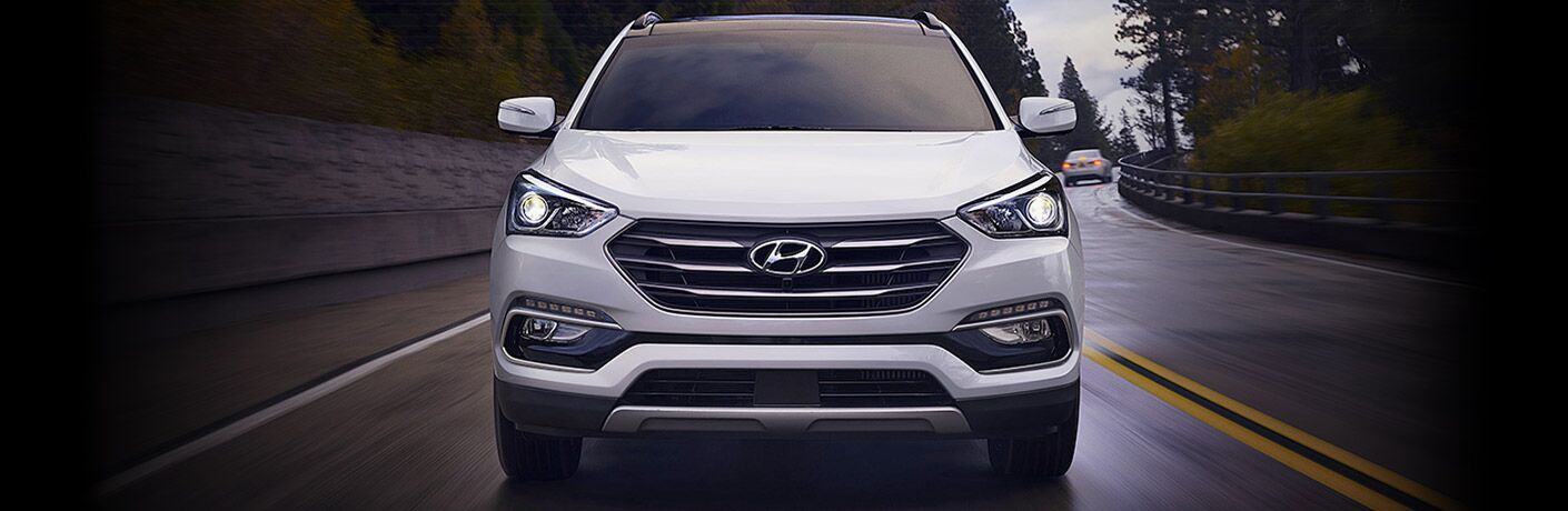 Exterior view of a silver 2017 Hyundai Santa Fe driving on a wet two lane road