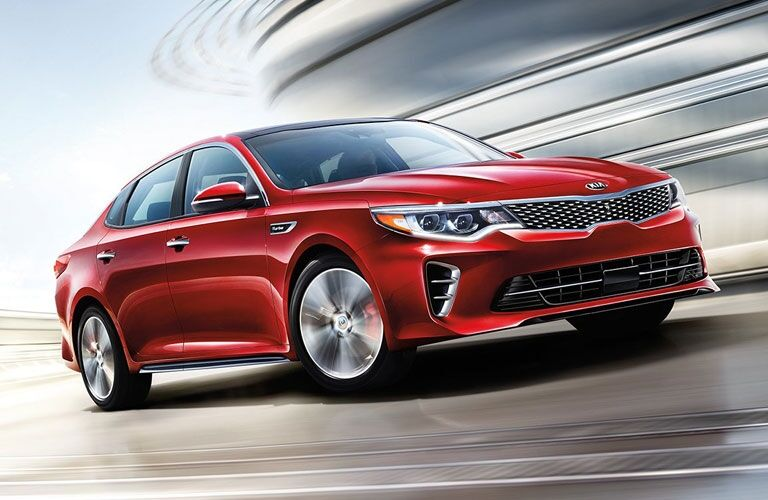Exterior view of a red 2017 Kia Optima driving around a race track
