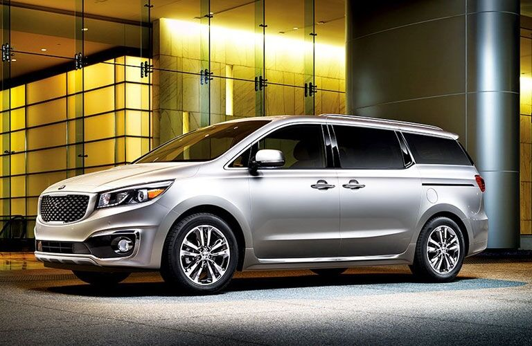 Exterior view of a silver 2017 Kia Sedona parked outside an office building