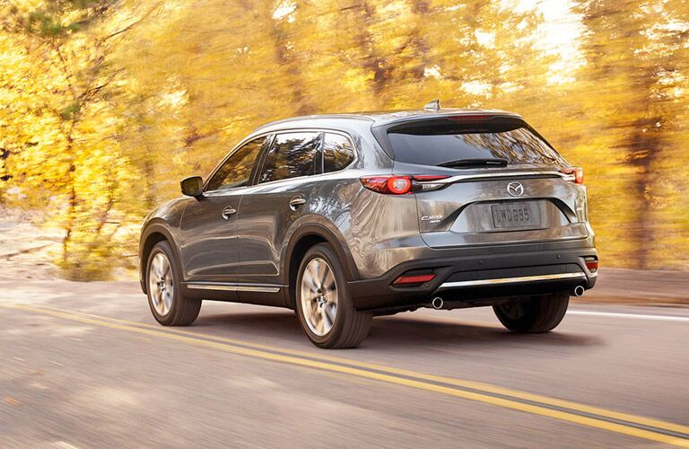 Exterior view of the rear of a grey 2017 Mazda CX-9 driving down a two-lane road