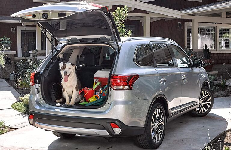 Exterior view of the rear of a 2017 Mitsubishi Outlander with the liftgate opened and the rear cargo area full of cargo and a cute dog