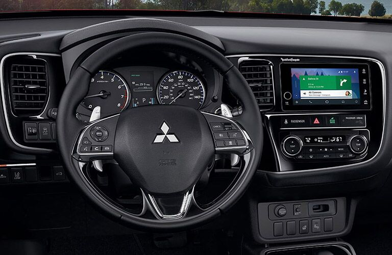 Interior closeup view of the steering wheel and touchscreen inside a 2017 Mitsubishi Outlander