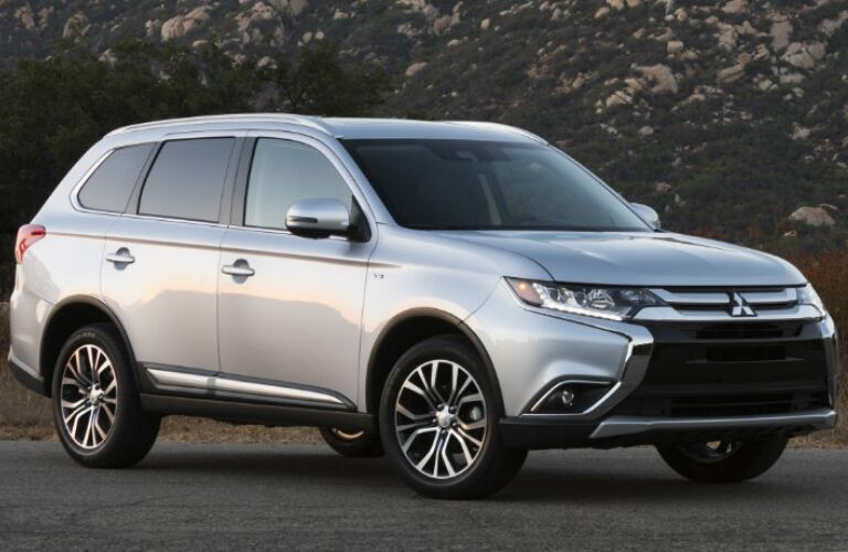 Exterior view of a silver 2017 Mitsubishi Outlander parked on a country road