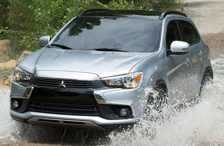 Exterior view of a silver 2017 Mitsubishi RVR driving through shallow water